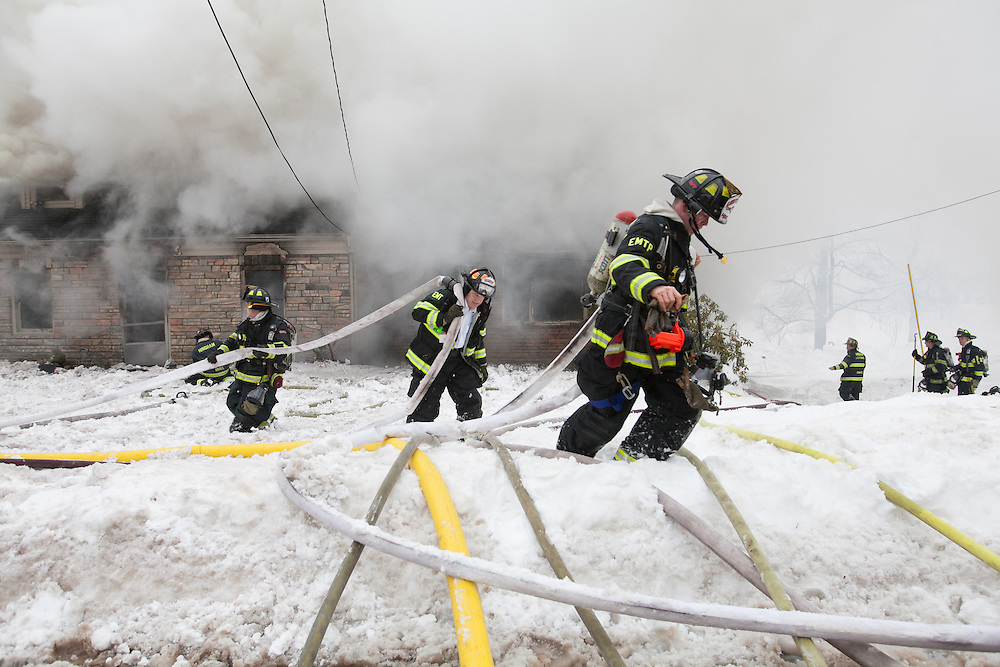 Hingham, MA 02/11/2013.Firefighters carry a hose line through heavy snow at the scene of a 3 alarm house fire on East St in Hingham on Monday..Alex Jones / www.alexjonesphoto.com