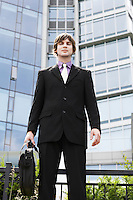Business man holding briefcase outside office portrait
