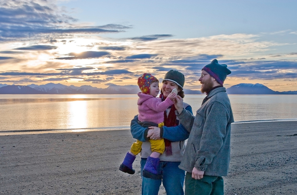 A young girls inspects a sea shell at sunset with her parents at the beach.