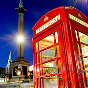 British public telephone box at Trafalgar Square. In the background is Nelson's Column and motion blur of lights of passing traffic.
