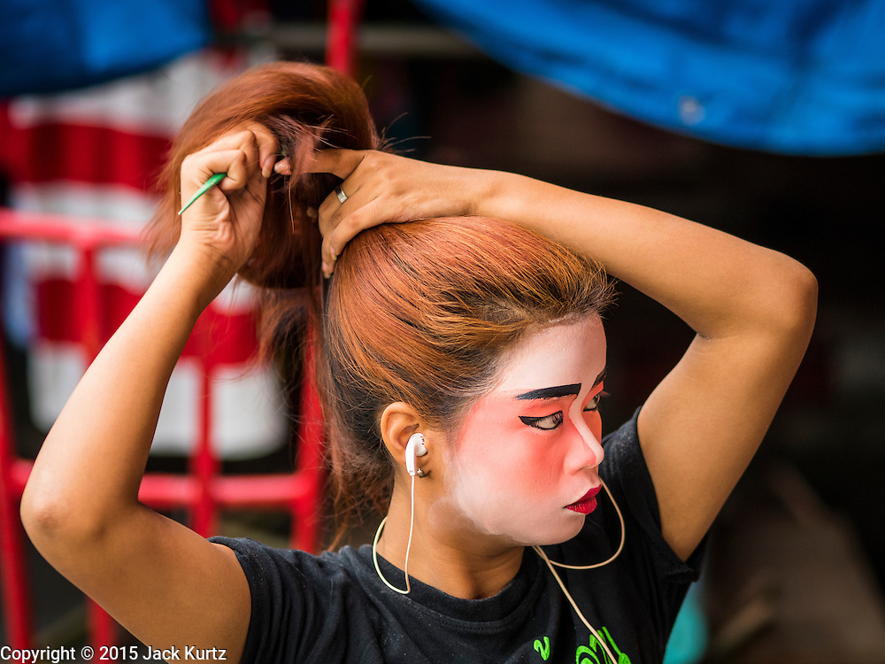 "14 MAY 2015 - BANGKOK, THAILAND:   A Chinese opera performer brushes out her hair before a show at the Pek Leng Keng Mangkorn Khiew Shrine in the Khlong Toey slum in Bangkok. Chinese opera was once very popular in Thailand, where it is called ""Ngiew."" It is usually performed in the Teochew language. Millions of Chinese emigrated to Thailand (then Siam) in the 18th and 19th centuries and brought their culture with them. Recently the popularity of ngiew has faded as people turn to performances of opera on DVD or movies. There are still as many 30 Chinese opera troupes left in Bangkok and its environs. They are especially busy during Chinese New Year and Chinese holiday when they travel from Chinese temple to Chinese temple performing on stages they put up in streets near the temple, sometimes sleeping on hammocks they sling under their stage. Most of the Chinese operas from Bangkok travel to Malaysia for Ghost Month, leaving just a few to perform in Bangkok.       PHOTO BY JACK KURTZ"