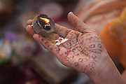 A woman's hand decorated with henna holds a candle and a jasmine flower during a prayer ceremony on the ghats by the river Ganges at Varanasi, Uttar Pradesh, India. The jasmine flower is an offering specific to the goddess Durga.