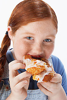 Overweight girl (13-15) Eating pastry portrait close-up