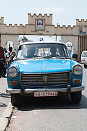 An old Peugeot, the typical car found in Harar, sits in front of the main gate to the walled city in Ethiopia.