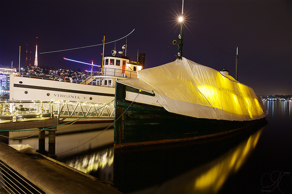 The historic Arthur Foss tugboat (1889) under wraps for winter alongside the Virginia V (1912) with the lights of Queen Anne hill in the background.