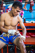 "18 DECEMBER 2104 - BANGKOK, THAILAND: A boxer wraps his hands before sparring at the Kanisorn gym in Thonburi. The Kanisorn boxing gym is a small gym along the Wong Wian Yai - Samut Sakhon train tracks. Young people from the nearby communities come to the gym to learn Thai boxing. Muay Thai (Muai Thai) is a Thai fighting sport that uses stand-up striking along with various clinching techniques. It is sometimes known as ""the art of eight limbs"" because it is characterized by the combined use of fists, elbows, knees, shins, being associated with a good physical preparation that makes a full-contact fighter very efficient. Muay Thai became widespread internationally in the twentieth century, when practitioners defeated notable practitioners of other martial arts. A professional league is governed by the World Muay Thai Council. Muay Thai is frequently seen as a way out of poverty for young Thais and Muay Thai camps and schools are frequently crowded. Muay Thai professionals and champions are often celebrities in Thailand.     PHOTO BY JACK KURTZ"