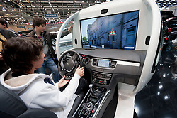 Visitor using Peugeot driving simulator maximise fuel efficiency at the Geneva Motor Show 2011 Switzerland