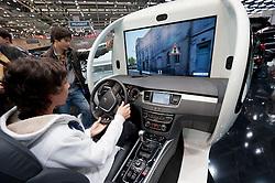 Visitor using Peugeot driving simulator maximise fuel efficiency at the Geneva Motor Show 2011 Switzerland