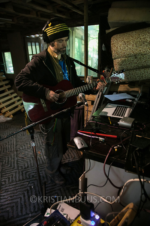 Adam Raynor making music in their communial space, using power from solar panel charged car batteries. Life in the Save Leith Hill camp in Coldharbour Lane. Europa Oil and Gas company has got license to drill for oil in the woods near Leith Hill.  Proetctors of the land, a group of local campaigners against the proposed drilling and activists have set up a community camp on Coldharbour Lane to  protect Leith Hill from the unconventional oil exploration, through monitoring, awareness raising, and peaceful community action.