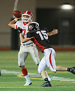 Washington's Charles Blades (7) looks for an open receiver as he is chased by Linn-Mar's Austin Burbridge (15) during the first quarter of the game between Cedar Rapids Washington and Linn-Mar at Linn-Mar Stadium in Marion on Friday, September 14, 2012.