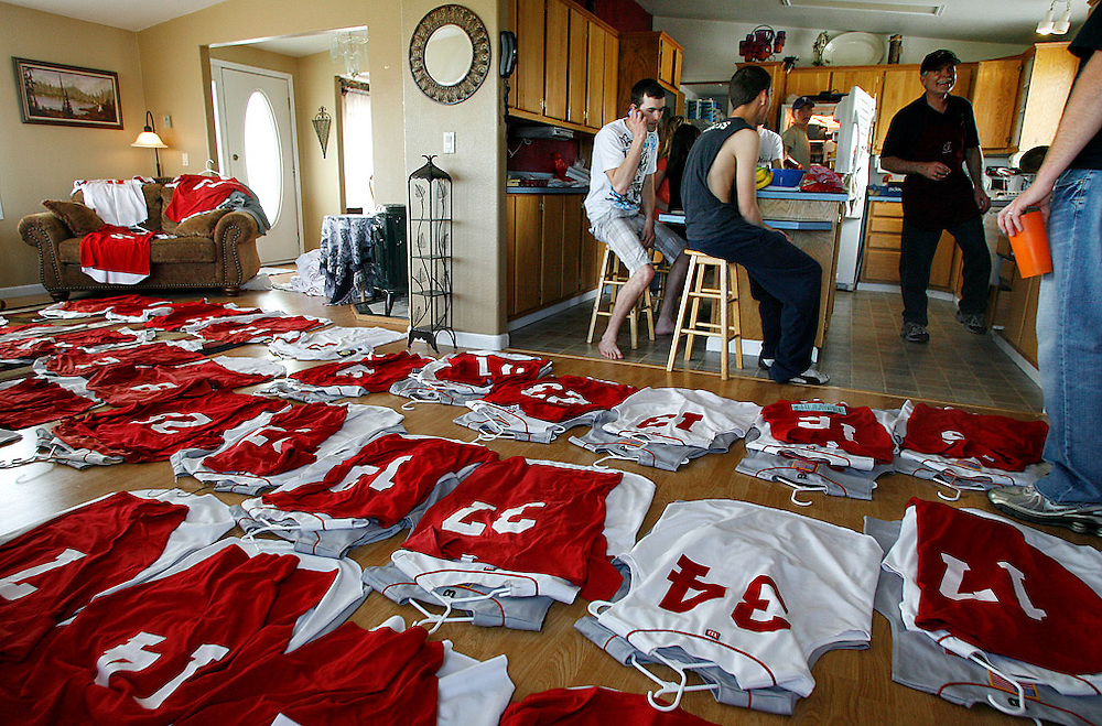 """The Burgesses prepare for a barbecue in the kitchen as uniforms for the Pasco Sun Devils American Legion baseball team fill the living room. Wayne, right, is the president of the board, and his wife Becky is the treasurerer. As the summer season approached, they had to take inventory and figure out which home and away jerseys needed replacing. Though Luke and Levi played for different teams during the high school season, Legion ball will give them one last time to play together. """"He'll probably be pitching, and I'll play outfield, backing him up when they hit bombs,"""" says Levi. """"Thanks, Levi,"""" says Luke. """"It'll be fun,"""" says Levi. """"We go back to being brothers."""" Luke, being a freshman on the senior team, will see limited playing time. """"I knew I wasn't going to play at all in Wenatchee,"""" he says. """"When Levi told me I might not be able to play, I just asked him if I could be in the dugout, at least. It was fun to sit in the dugout with all the guys, and I was actually nervous."""""""