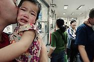 Au centre medicale de l'ile de Shamian a Canton, Tate (2 ans et demi) en larme dans les bras de son pere adoptif Nate.Tate traumatisee par le vaccin anti tuberculeux de la veille est revenue avec son pere pour verifier l'efficacite du vaccin. Nate vient du Minnesota, il a adopte Tate avec son epouse Tomme. Tate est leur 3eme enfant et premiere adoption.