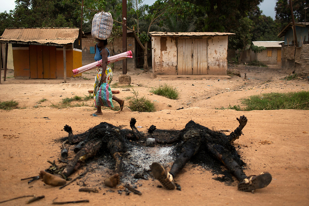 ATTENTION EDITORS - VISUAL COVERAGE OF SCENES OF INJURY OR DEATH<br /> <br /> A woman passes charred bodies while fleeing with her belongings during one of the latest incidents of sectarian violence in the capital Bangui January 28, 2014.