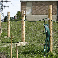 A fence with a hose set up at a community garden.