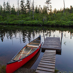 "A canoe and boat dock on the Cold Stream ""deadwater"" above Upper Cold Stream Falls in Maine's Northern Forest. Johnson Mountain Township."