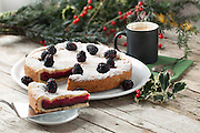Trifle filled cake and mug with hot coffee on Christmas table decorated with holly.