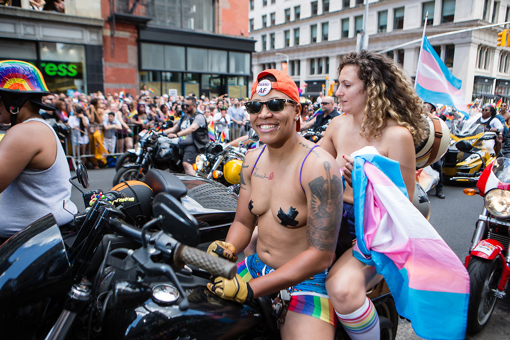 """New York, NY - 30 June 2019. The New York City Heritage of Pride March filled Fifth Avenue for hours with participants from the LGBTQ community and it's supporters. Motorcycles led the march, the driver of this cycle wearing a button reading """"Trans AF."""""""