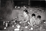 In a walk-up apartment in Kathmandu, a Nepali mother cooks dinner for her two sons on a one-burner kersosine stove. Toned black and white image.