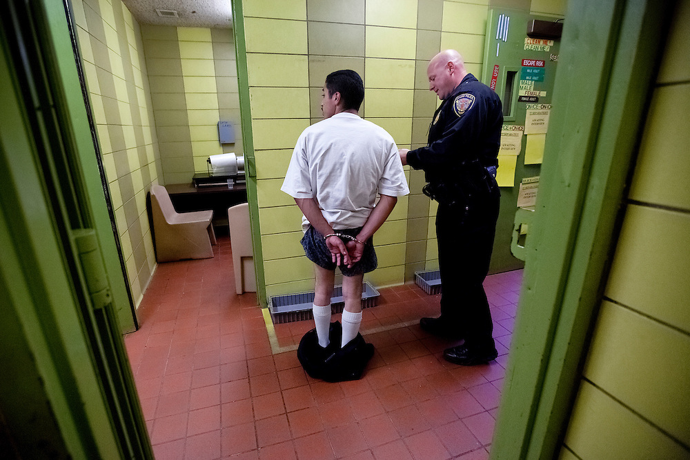 Officer Don Ehrhardt searches a gang member during the initial arrest phase at the city jail. Dec. 6, 2011. Oxnard, Calif. (Photo by Gabriel Romero ©2011)