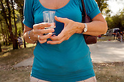 woman with empty plastic wine glass at an outdoor picnic happening