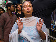 05 OCTOBER 2014 - GEORGE TOWN, PENANG, MALAYSIA:  A woman prays in the street during a procession honoring Durga in George Town during the Navratri procession. Navratri is a festival dedicated to the worship of the Hindu deity Durga, the most popular incarnation of Devi and one of the main forms of the Goddess Shakti in the Hindu pantheon. The word Navaratri means 'nine nights' in Sanskrit, nava meaning nine and ratri meaning nights. During these nine nights and ten days, nine forms of Shakti/Devi are worshiped.   PHOTO BY JACK KURTZ