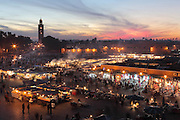 Nighttime view of stalls at Djemma el Fna square and marketplace, Medina, Marrakech, Morocco. The minaret of the Koutoubia mosque towers over the square. Picture by Manuel Cohen