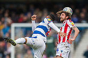 Massimo Luongo (Queens Park Rangers) heads the ball beyond the reach of Joe Allen (Stoke) during the EFL Sky Bet Championship match between Queens Park Rangers and Stoke City at the Loftus Road Stadium, London, England on 9 March 2019.