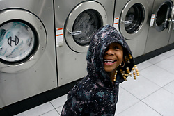Egypt, 7 and (not pictured) Dianne, 12, play hide-and-seek around the isles of laundromats while their mother, Venita Bracy does the laundry, at the laundromat owned and operated by James Betterson, in NorthEast Philadelphia, on February 15 2019. (Bastiaan Slabbers for WHYY)