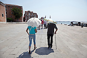 tourists walking on the Riva degli Schiavoni during a hot day in Venice Italy