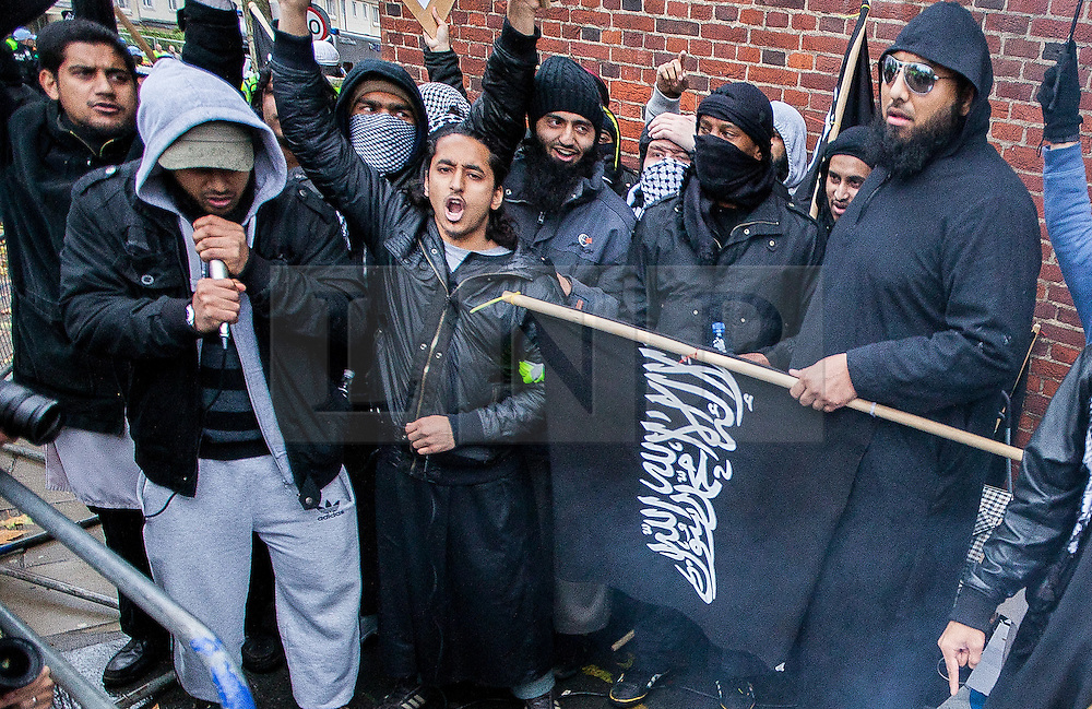 "© Licensed to London News Pictures . London , UK . MOHAMMED REZA HAQUE (known as "" Giant "" ) (right, wearing sunglasses) and SIDDHARTHA DHAR (known as "" Jihadi Sid "" )(top left) in front of a burning poppy at a Muslims Against Crusades demonstration on Exhibition Road in London , on the anniversary of Armistice Day , 11th November , in 2010 . Haque and Dhar are believed to be two of five executioners featured on a recent ISIS video filmed in Syria . Photo credit : Joel Goodman/LNP"