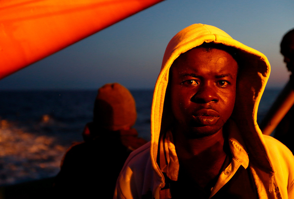 A migrants stands on the deck of the Medecins san Frontiere (MSF) ship Bourbon Argos off the coast of Libya at dusk August 7, 2015.  Some 241 mostly West African migrants on the ship are expected to arrive on the Italian island of Sicily on Sunday, according to MSF.<br /> REUTERS/Darrin Zammit Lupi <br /> MALTA OUT. NO COMMERCIAL OR EDITORIAL SALES IN MALTA