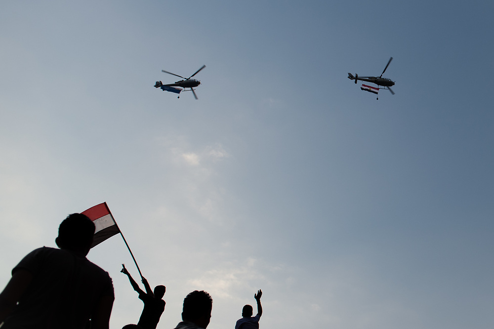 During a large anti-Morsi rally, protesters greet Egyptian military helicopters as they flew over Tahrir Square. Cairo, Egypt, July 1, 2013