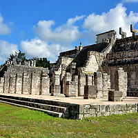 Temple of the Warriors at Chichen Itza, Mexico<br /> Templo de los Guerreros was built upon the site of a previous temple honoring Chacmool, a reclining warrior found only at Chichen Itza and at Tula, the former Toltec civilization capital about 750 miles away near today's Mexico City. A statue of Chacmool – considered to be a messenger of the gods - rests atop this three-level stepped pyramid. Among the fascinating features are 200 square columns with carvings portraying Toltec warriors. Also notice the sculptures perched on either side of the staircase standing above the feathered serpent heads. They were used as flag bearers. The massive Temple of the Warriors dates from the Early Postclassic period (950 – 1200 AD).