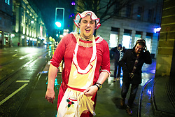 "© Licensed to London News Pictures . 21/12/2018 . Manchester , UK . A man walks along Cross Street wearing a Mrs Claus inspired outfit . Revellers out in Manchester City Centre overnight during "" Mad Friday "" , named for historically being one of the busiest nights of the year for the emergency services in the UK . Photo credit : Joel Goodman/LNP"
