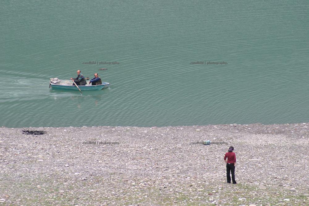 Ein Fischerboot am Ufer des Schinwali Sees an der Georgischen Heerstrasse. Die Fischer beobachten eine junge Frau am Ufer. © Timo Vogt