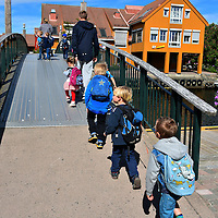 Row of Children Walking Over Footbridge in Kristiansand, Norway <br /> There is something endearing about watching a row of children walking in a row during a fieldtrip while being chaperoned by adults. It always reminds me of geese struggling to keep their goslings in line.  These kids were marching over a footbridge leading to Fiskebrygga, a former fish market that has been converted into an entertainment district.