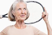 Senior woman holding tennis racket over her shoulder against white background
