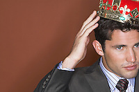 Man putting on crown against brown background close-up