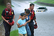 Members of the Tyler FD, firefighters Jason Beasley(l) and Joey Hooton rescue an unidentified woman and a child after their car stranded under the bridge at the corner of Ferguson and Bonner in Tyler on Tuesday July 3, 2007 Photo: Jaime R. Carrero/Tyler Morning Telegraph
