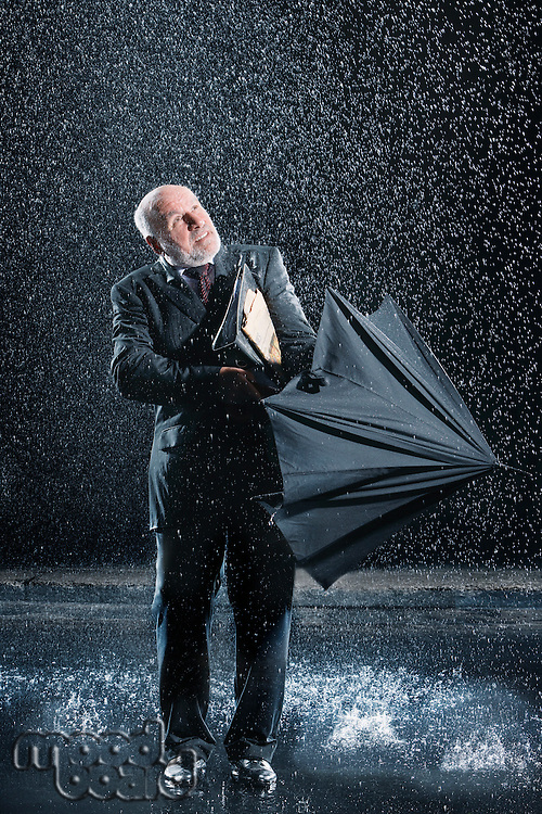 Businessman struggling to open umbrella during Sudden Rain