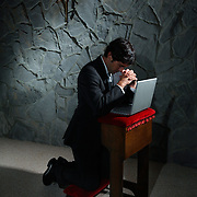 Businessman prays on bench with laoptop - illustration of tech support, computer problems/ (D.Mciver model)
