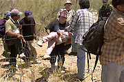 A 6-year-old girl is hoisted through a fence by her aunt after the group they were traveling with was apprehended by the U. S. Border Patrol east of Sells on the Tohono O'odham Nation in Arizona, USA. The group crossed illegally from Mexico two days earlier and walked through the Sonoran Desert in temperatures exceeding 110 degrees in the deadliest stretch along the border.