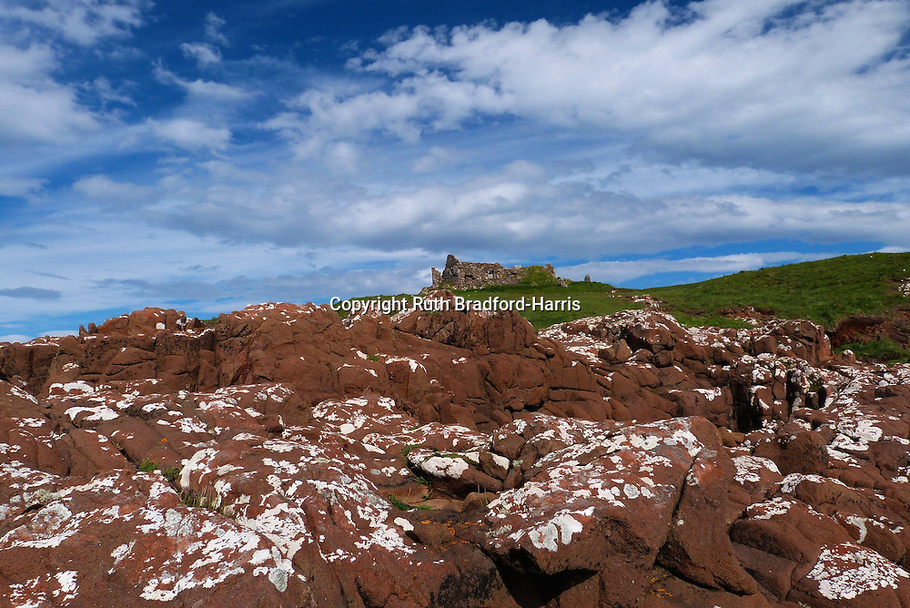 A dramatic panoramic skyscape with billowing cumulus clouds in a deep blue sky over the ruins of Duntulm Castle from Ru Meanish, Isle of Skye. In the foregound on the shore are hexagonally jointed Basalt dykes of a strikingly red colour.<br /> <br /> Date taken: 14 June 2016.