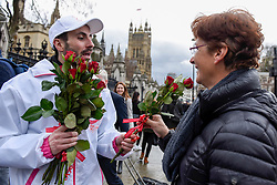 "© Licensed to London News Pictures. 08/03/2017. London, UK. A woman receives roses.  A flashmob takes place in Parliament Square as part of International Women's Day.  Apparently backed by the Russian government, a giant balloon is unsuccessfully inflated bearing the text ""From Russia With Love"" and ""#makehersmile"" with organisers handing out roses to unsuspecting female passers by. Photo credit : Stephen Chung/LNP"