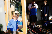Naomi Martin, 43, (right) and Simon Courage, 43, (centre) are portrayed in their house on the first day back to school for their children Claudia, 10, (centre) and Louis,4, (left) in BedZED on Thursday, Sep. 6, 2007, London, UK. BedZED or the Beddington Zero Energy Development, is an environmentally-friendly housing development near Wallington, England in the London Borough of Sutton. It was designed by the architect Bill Dunster who was looking for a more sustainable way of building housing in urban areas in partnership between the BioRegional Development Group and the Peabody Trust. There are 82 houses, 17 apartments and 1,405 square meters of work space were built between 2000. The project was shortlisted for the Stirling Prize in 2003. The project is designed to use only energy from renewable source generated on site. In addition to 777 square meters of solar panels, tree waste is used for heating and electricity. The houses face south to take advantage of solar gain, are triple glazed and have high thermal insulation while most rain water is collected and reused. Appliances are chosen to be water efficient and use recycled water wherever possible. Low impact building materials were selected from renewable or recycled sources and were all originating within a 35 mile radius of the site to minimize the energy required for transportation. Also, refuse collection facilities are designed to support recycling and the site encourage eco-friendly transport: electric and LPG cars have priority over petrol/diesel cars, and electricity is provided by parking spaces appositely built for charging electric cars.