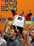 "KING OF PRUSSIA, PA.- MAY 31:  Todd Newton, host of the Game Show Network's ""Whammy"" wears a Philadelphia Flyers jersey, cheers as he tapes a commercial promoting the Game Show Network, during the Game Show Network's ""Get Schooled Tour"" at the King of Prussia Mall May 31, 2003 in King of Prussia, Pennsylvania. Ninety people competed in a live game show to win $10,000 towards college tuition. (Photo by William Thomas Cain/Game Show Network via Getty Images)"