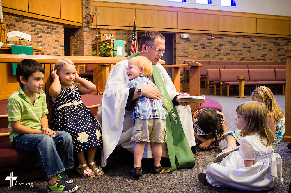 The Rev. Jonathan Huehn, associate pastor, receives a hug from his son Andrew as he leads a children's message Sunday, July 27, 2014, during worship at Christ Lutheran Church in Normal, Ill. LCMS Communications/Erik M. Lunsford