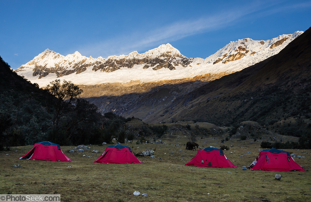 Day 2 of 10 days around Alpamayo: Sunrise hits peaks over Paria campground tents at 3800 meters or 12,500 feet elevation in Huaripampa Valley, Huascaran National Park (UNESCO World Heritage Site), Cordillera Blanca, Andes Mountains, Peru, South America.