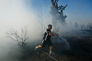 ORIG  Rob Kerr / The Bulletin<br /> Dave Vitelle, a firefighter from Burns, Ore. who responded locally to the [xxxx} fire, battles the blaze as it moves towards homes on the SE edge Monday afternoon.