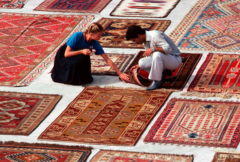 TURKEY, ISTANBUL Anatolian carpets displayed for a buyer in the plaza below the Sultan Ahmet Camii also called the Blue Mosque